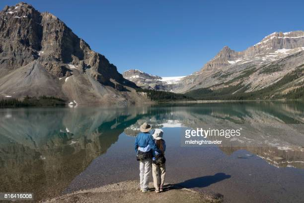 Woman man couple enjoy Bow Lake reflections Banff National Park Alberta Canada glacier
