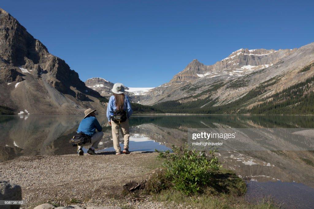 Woman man enjoy Bow Lake reflections Banff National Park Alberta Canada glacier : Stock Photo