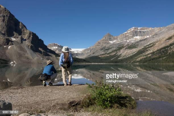 Woman man enjoy Bow Lake reflections Banff National Park Alberta Canada glacier