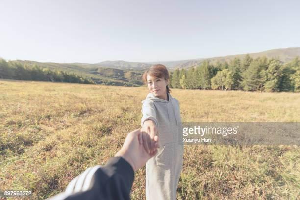 woman, man holding hand of girlfriend - following moving activity stock pictures, royalty-free photos & images