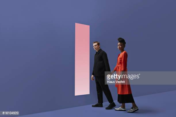 woman & man holding hands, approaching rectangular opening in coloured wall - overcoat stock pictures, royalty-free photos & images