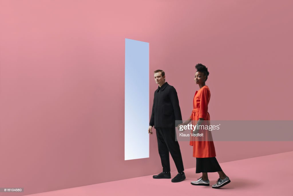 Woman & man holding hands, approaching rectangular opening in coloured wall : Stock Photo