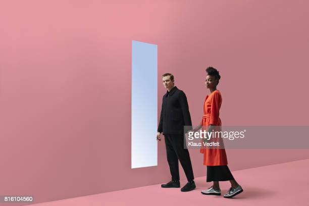 woman & man holding hands, approaching rectangular opening in coloured wall - 接近する 女性 ストックフォトと画像