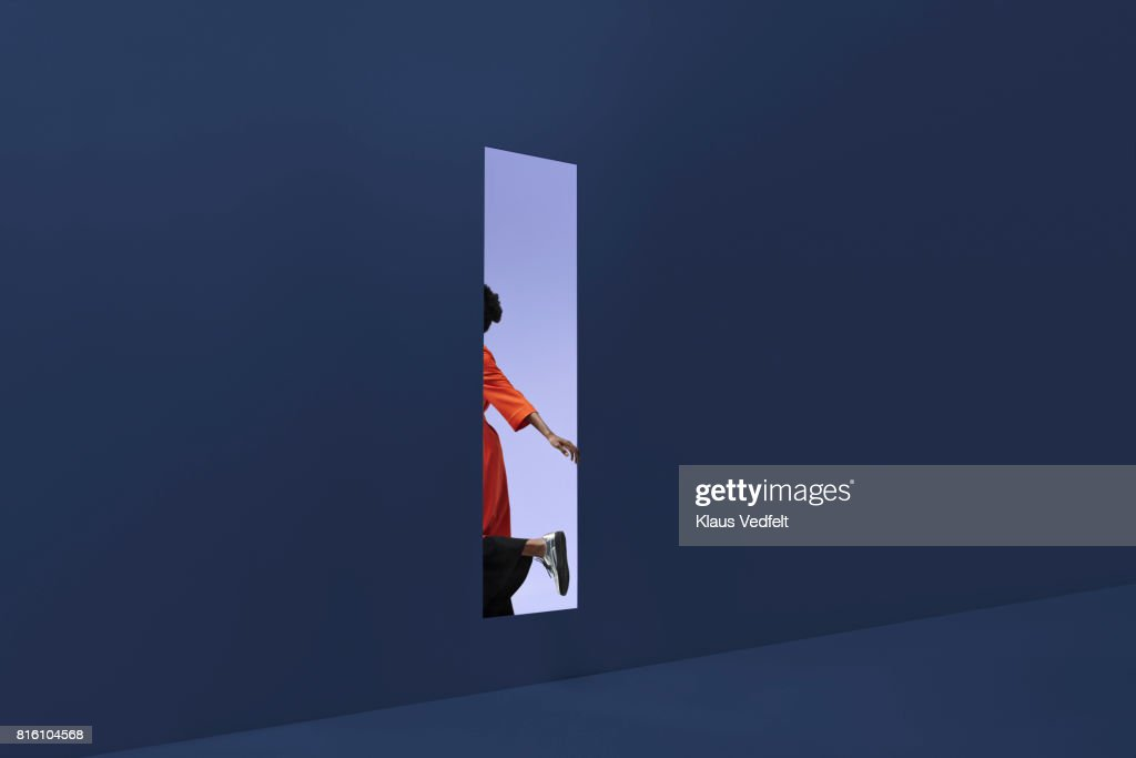 Woman & man holding hands, approaching rectangular opening in coloured wall : Foto stock