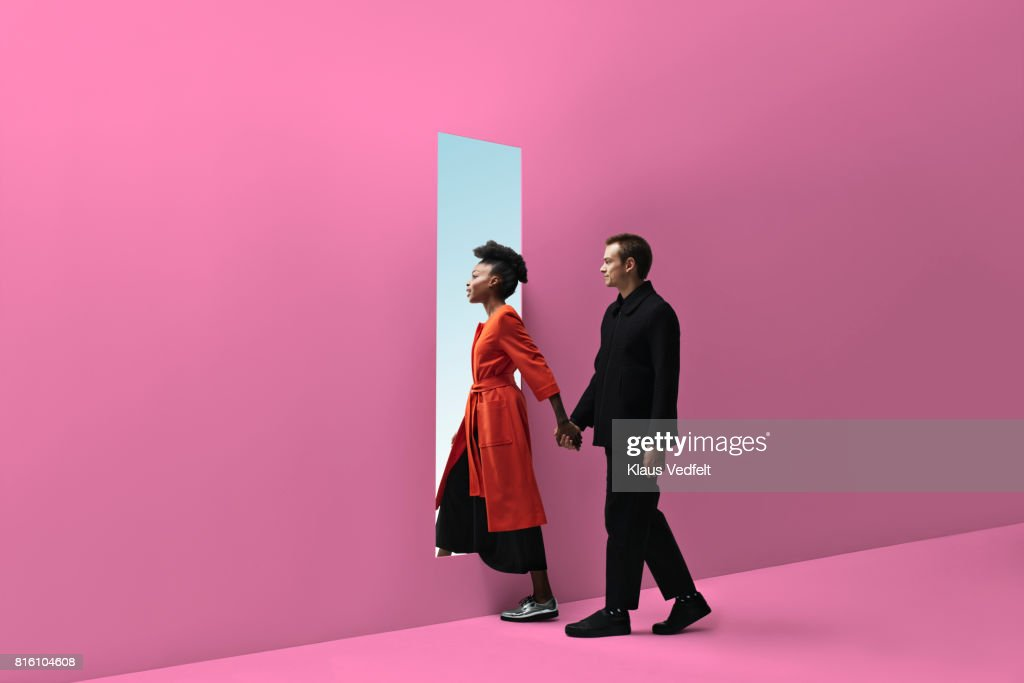 Woman & man holding hands, approaching rectangular opening in coloured wall : ストックフォト