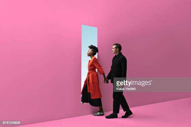 Woman & man holding hands, approaching rectangular opening in coloured wall