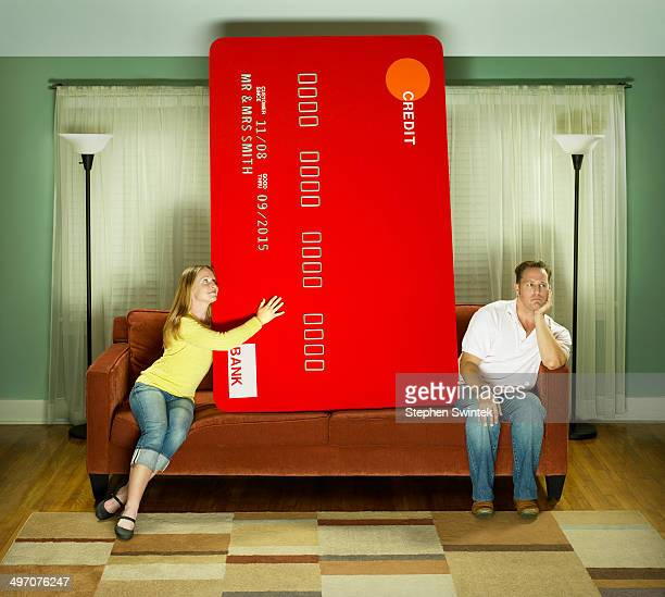 Woman & man & oversized credit card on couch