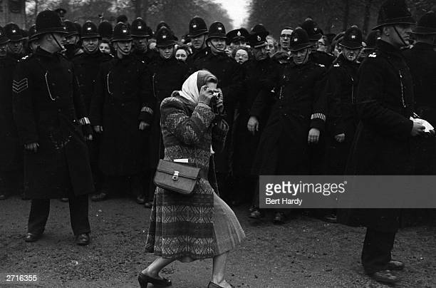 A woman manages to break through the line of policemen to take a photograph as the crowds wait for a glimpse of the newly married Princess Elizabeth...