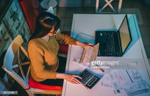 mujer gestionando las finanzas familiares por la noche - henri coste fotografías e imágenes de stock