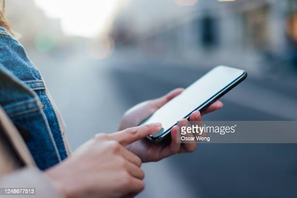 woman managing online banking using mobile app on smartphone - telephone stock pictures, royalty-free photos & images