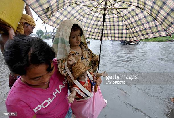 A woman maneouvers a flooded street carrying religious statues following heavy downpours in suburban Malabon city north of Manila July 16 2009 Heavy...