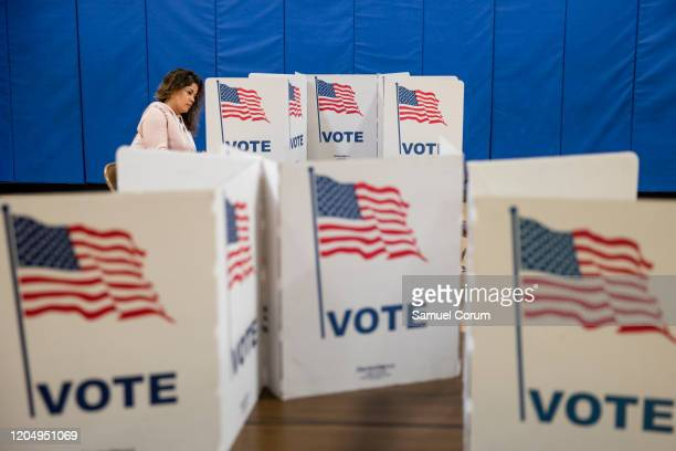 A woman marks down her vote on a ballot for the Democratic presidential primary election at a polling place in Armstrong Elementary School on Super...