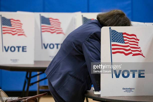 Woman marks down her vote on a ballot for the Democratic presidential primary election at a polling place in Armstrong Elementary School on Super...