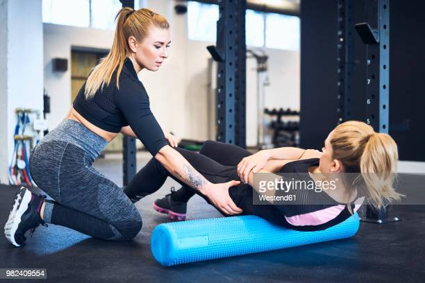 woman massages muscles with personal trainer after gym workout - massage rooms photos et images de collection