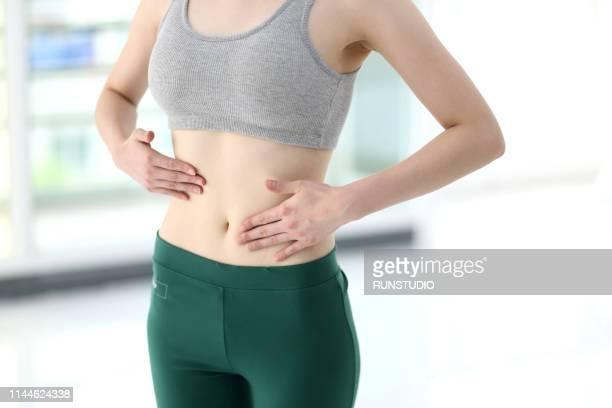 woman massaging belly - ブラトップ ストックフォトと画像