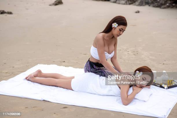 woman massaging customer lying at beach against sky - cleavage stock pictures, royalty-free photos & images