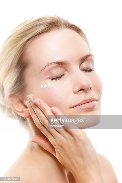 Woman massaging face with facial cream