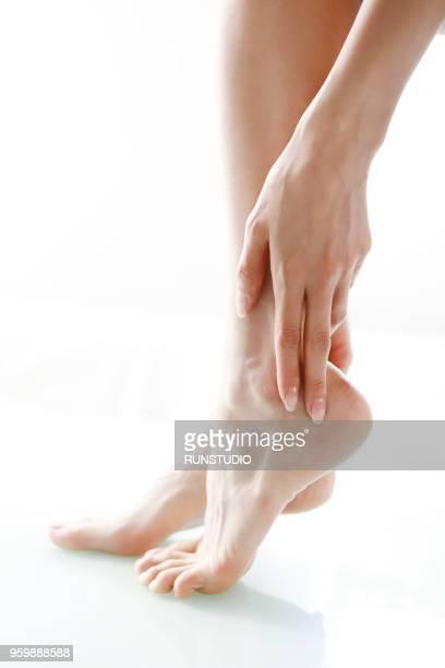 Woman massaging feet, low section