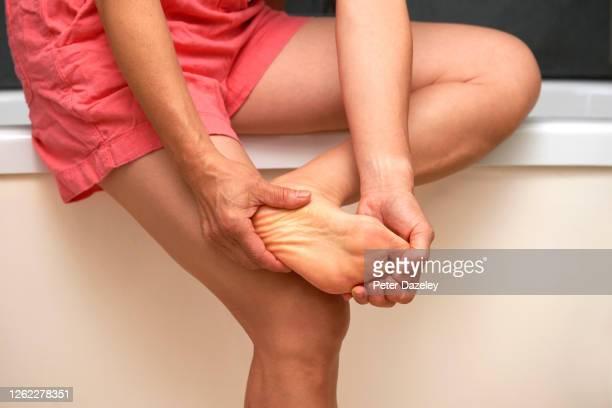 woman massaging foot - 人のつま先 ストックフォトと画像