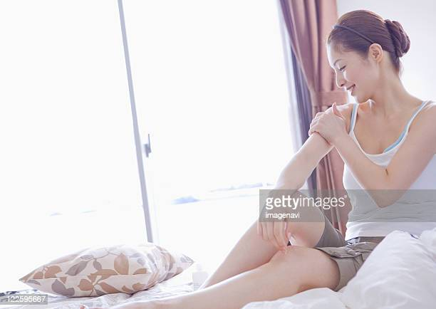 woman massaging her arms - camisole stock photos and pictures
