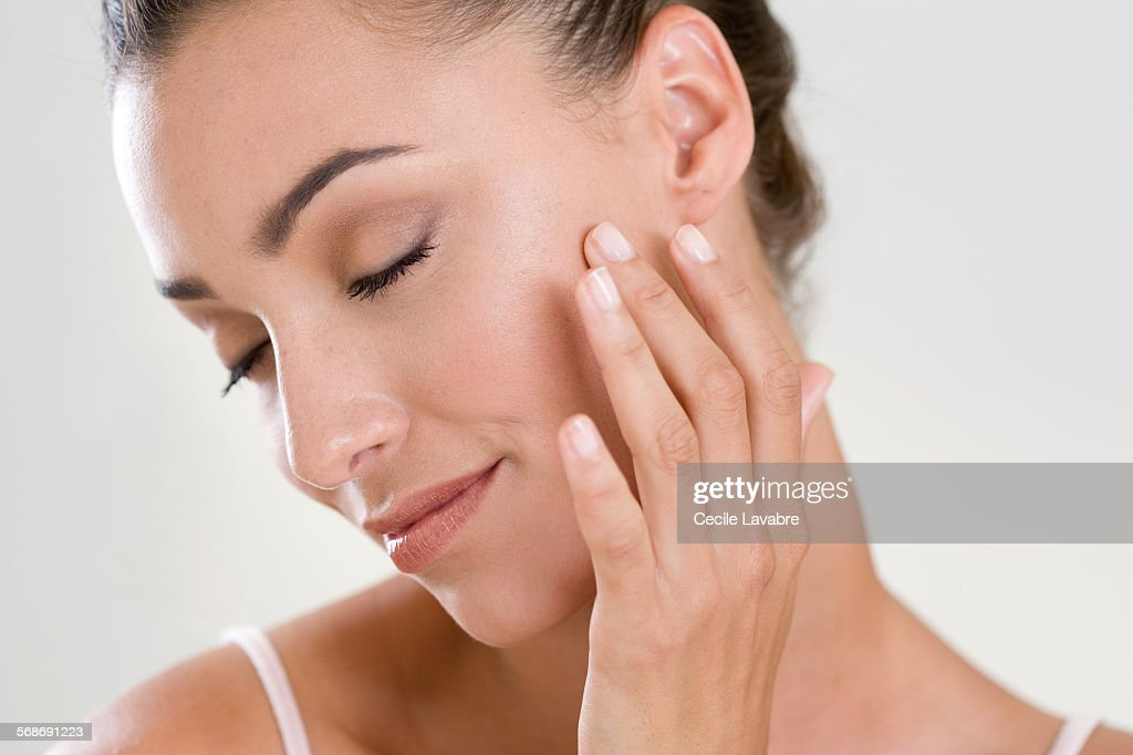 Woman massaging her face with finger : Stock Photo