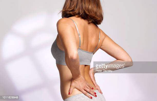 woman massaging her painful back due to sports injury - セミヌード ストックフォトと画像