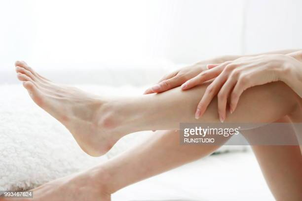 woman massaging legs - japanese women feet stock photos and pictures