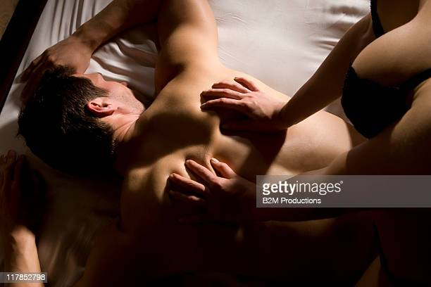 woman massaging man's back in bed - sensual massage stock photos and pictures