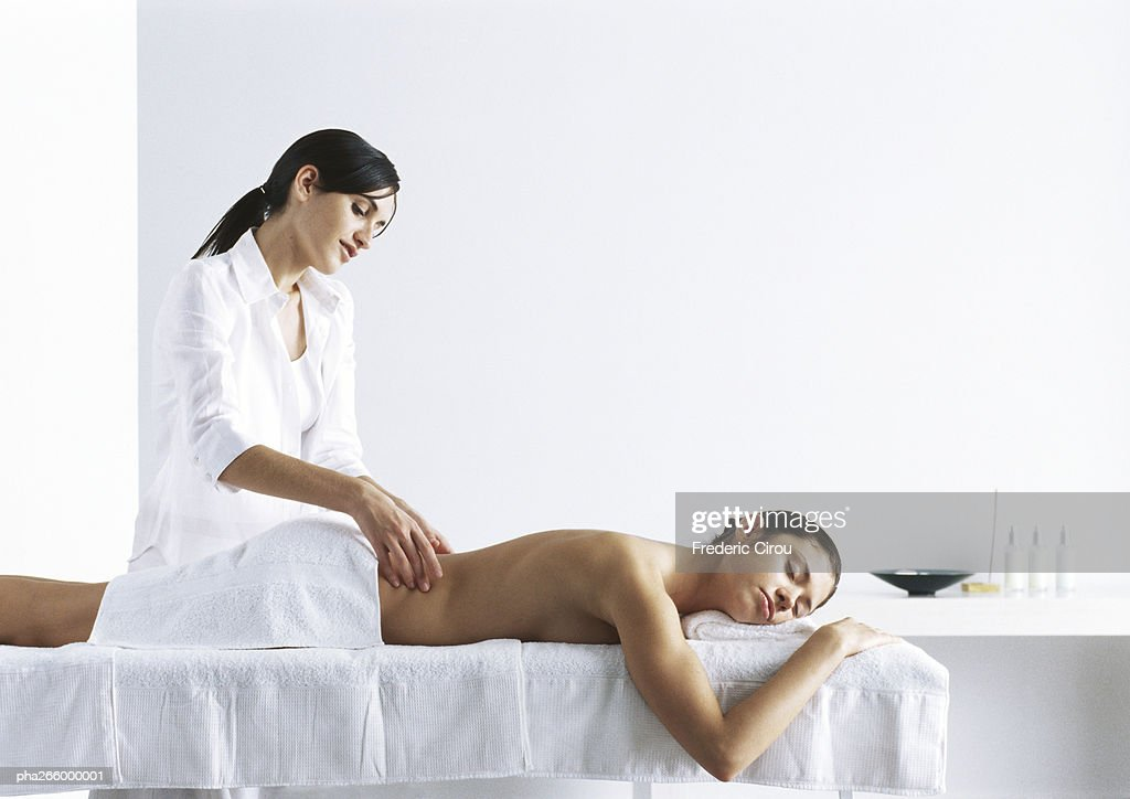 Woman massaging second woman on massage table : Stock Photo