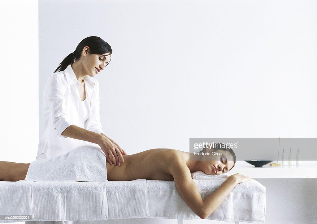 Woman massaging second woman on massage table : Stock Photo