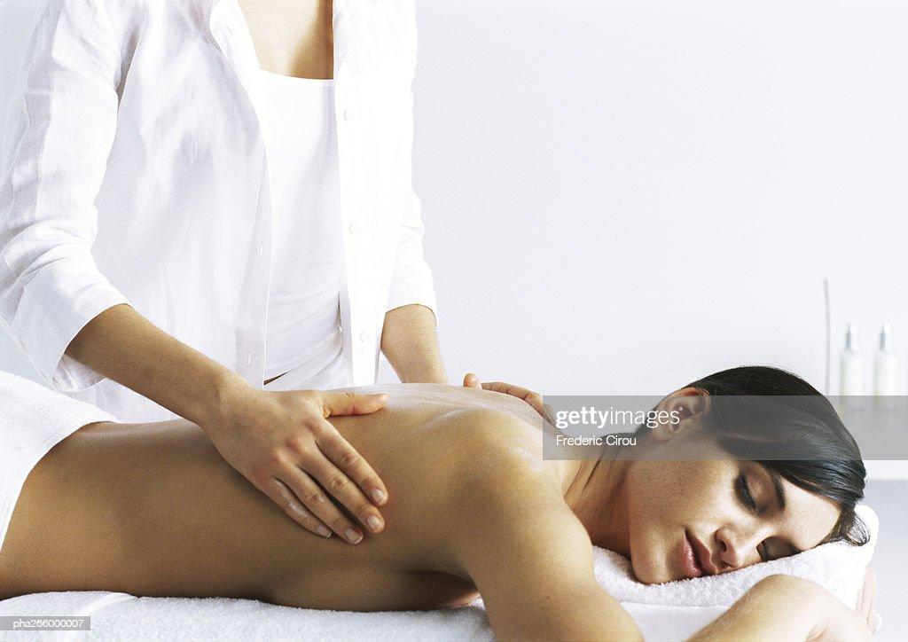 Woman massaging second woman on massage table : Stockfoto