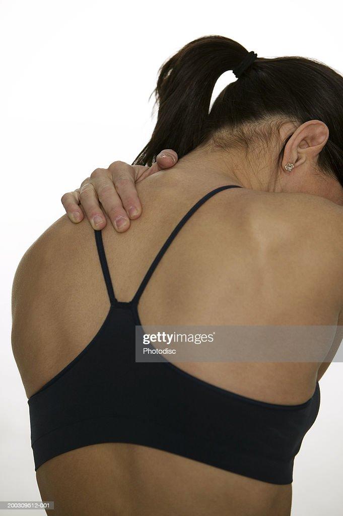 Woman massaging shoulder, in studio, rear view : Stock Photo