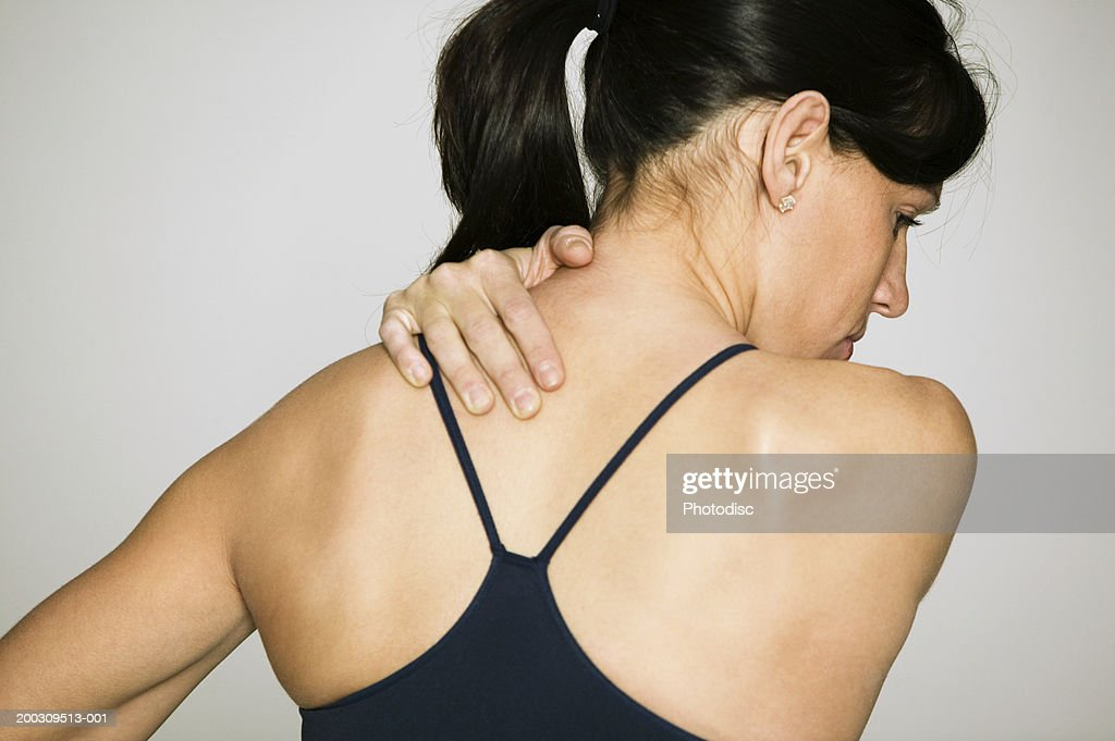 Woman massaging shoulder, in studio, rear view : Stock Photo