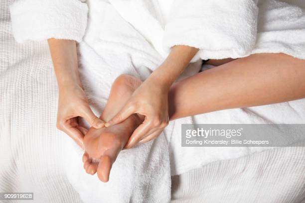 woman massaging sole of her foot - reflexology stock pictures, royalty-free photos & images