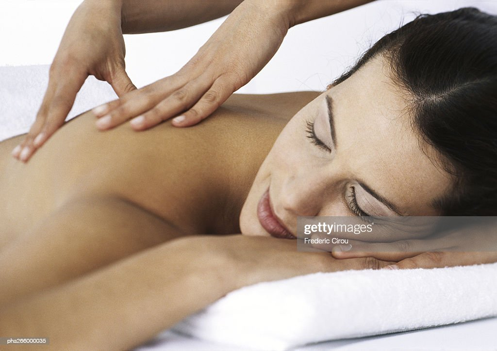 Woman massaging woman lying on stomach with eyes closed : Stockfoto