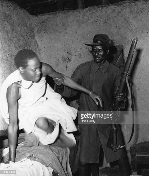 A woman Mau Mau suspect being hauled out of bed by a member of the Kenyan police Original Publication Picture Post 6223 Mau Mau Get Out Get Out pub...