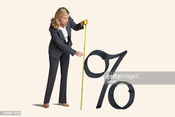 woman measures inflation or rising interest rates - percentage sign stock pictures, royalty-free photos & images