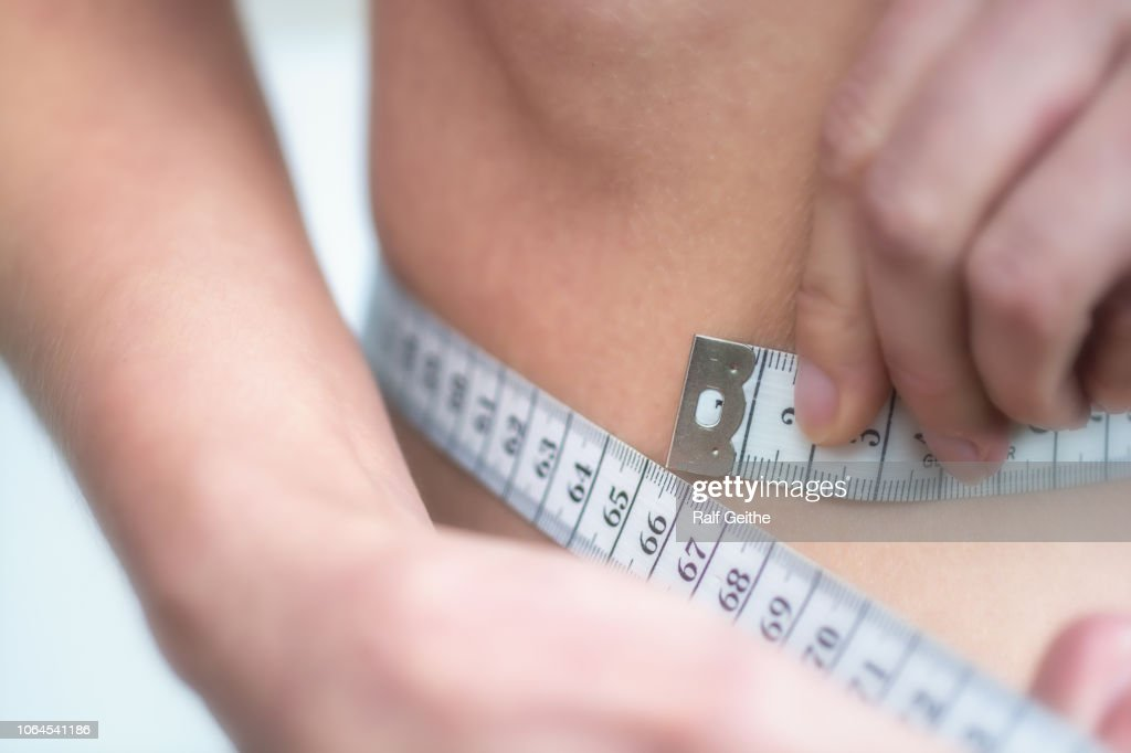 Woman measures very thin waist with measuring tape : Stock Photo