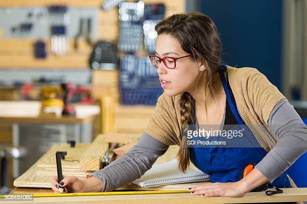 Mulher medidas de madeira na oficina