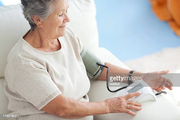 Woman measuring blood pressure at home.