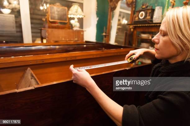 Woman Measuring Furniture At Store