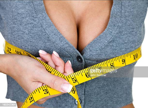 woman measuring her breast size - huge cleavage stock photos and pictures