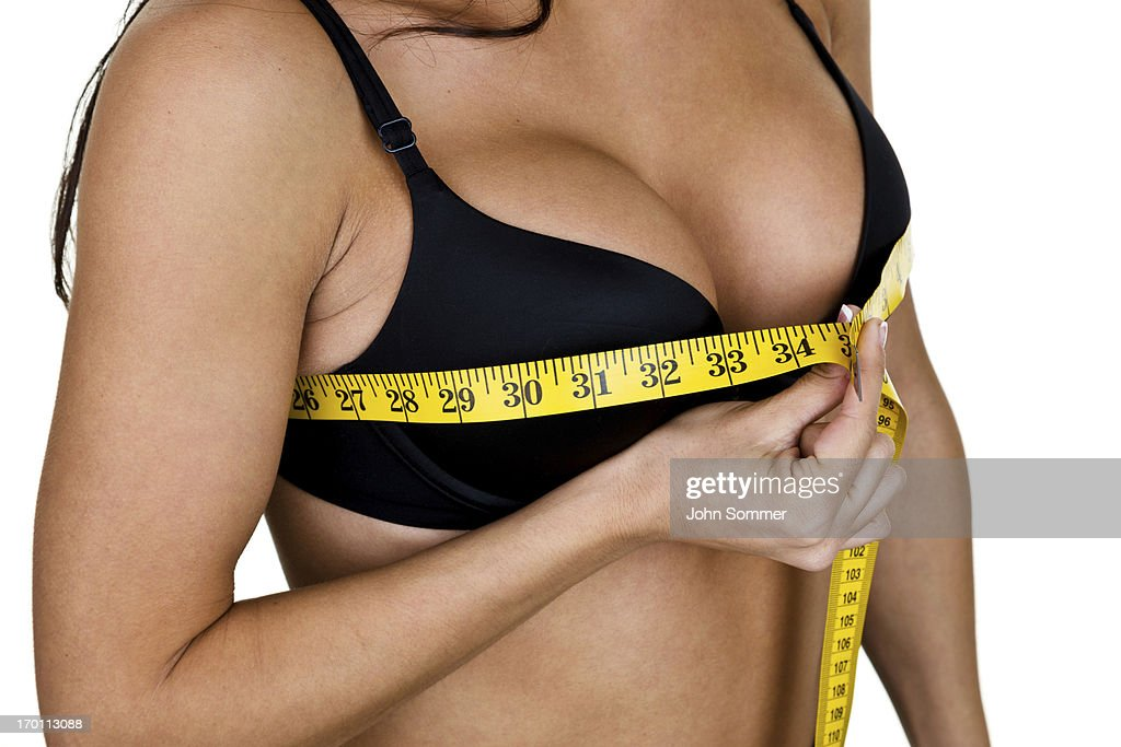 Woman measuring her breast size : Stock Photo