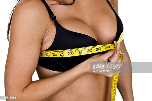woman measuring her breast size - big cleavage stock photos and pictures
