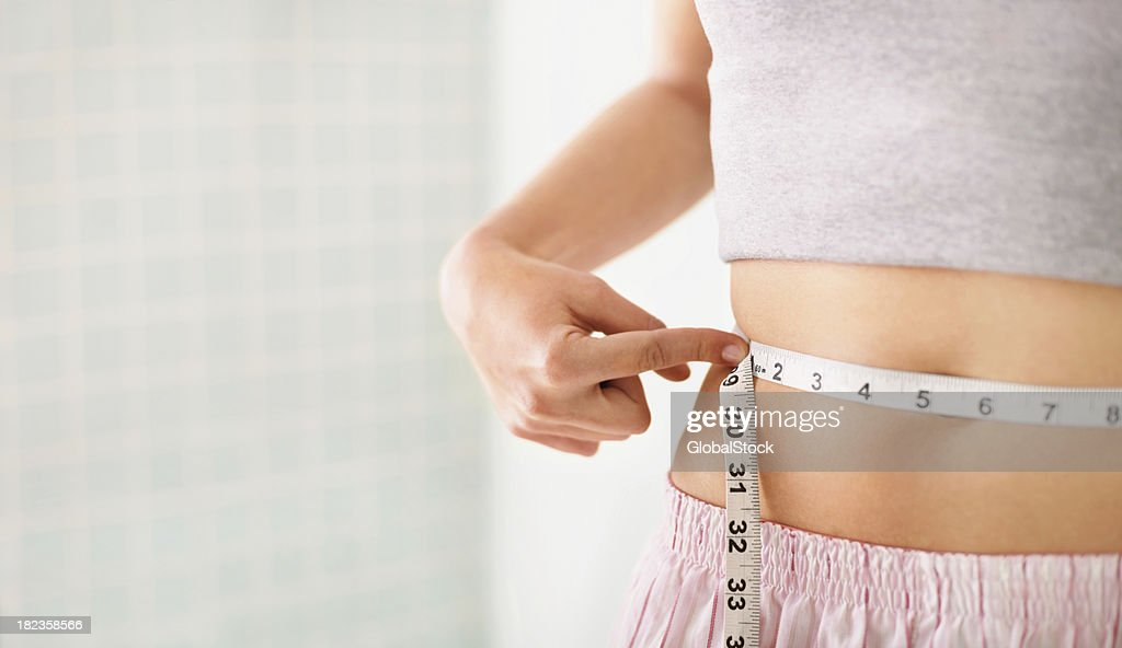 Woman measuring her waist over white : Stock Photo