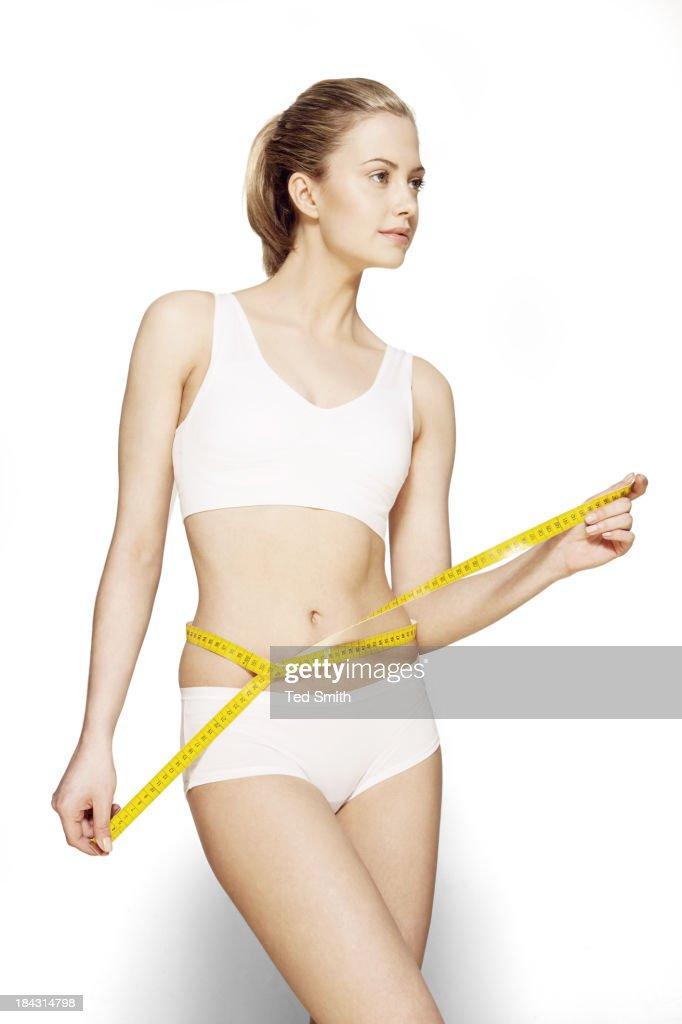 Woman measuring her waist : Stock Photo