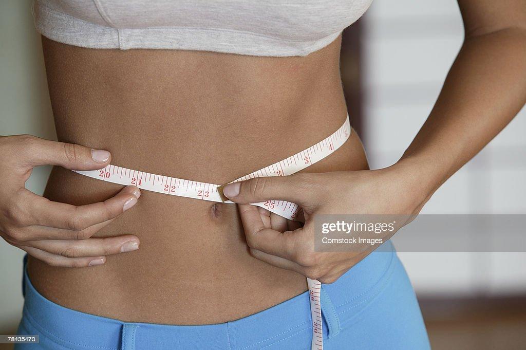 Woman measuring her waist : Stockfoto