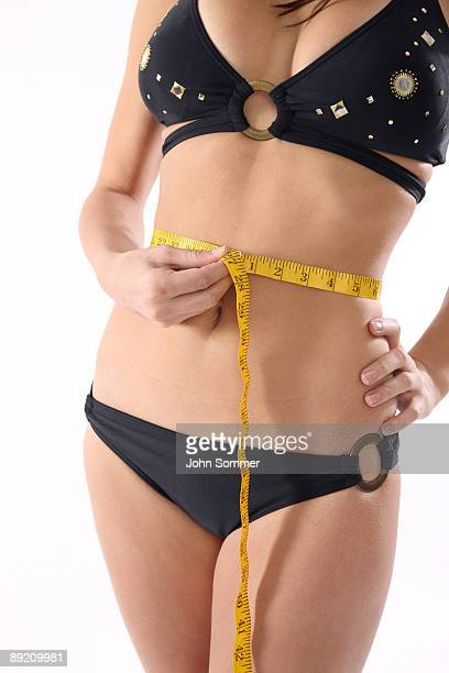woman measuring her waist - liposuction stock photos and pictures