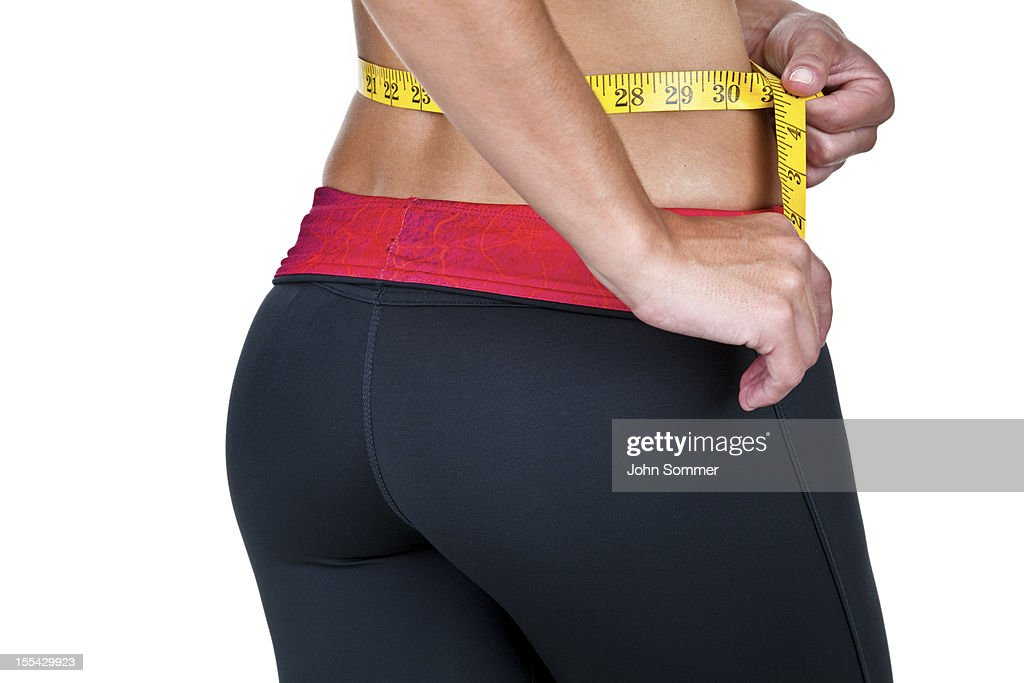 Woman measuring her waist shot from behind : Stock Photo
