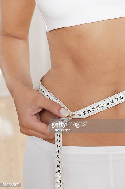 woman measuring her waistline - センチメートル ストックフォトと画像